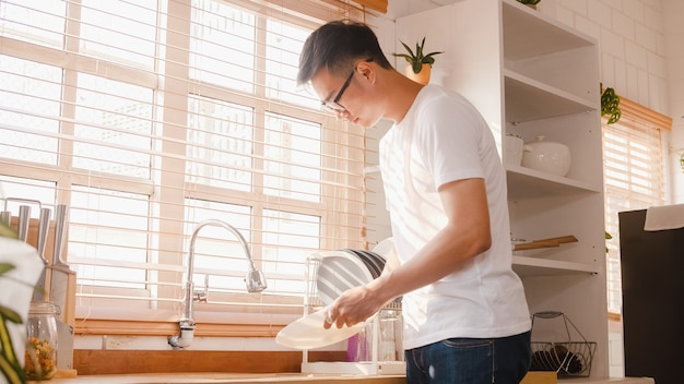 Happy young asian guy washing dishes while doing cleaning in the kitchen at house