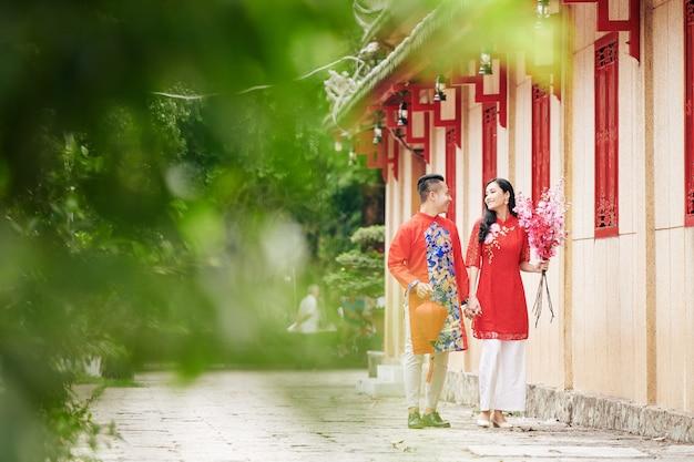 행복한 젊은 아시아 남편과 아내는 봄 축제 기간 동안 거리를 걷고 실크 랜턴과 복숭아 가지를 들고 손을 잡고 서로를 바라보고 있습니다.