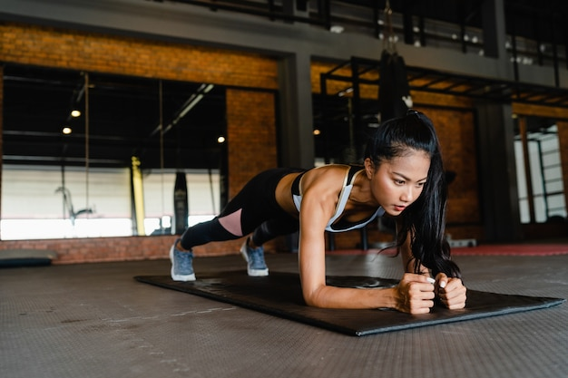 Happy young asian lady doing plank fat burning workout in fitness class