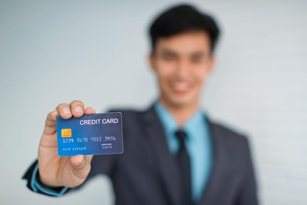 カメラに微笑んで、灰色の壁に対してクレジットカードを示す幸せな若いアジア人男性起業家