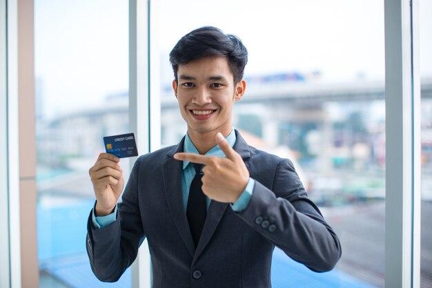 カメラに微笑んでクレジットカードをデモンストレーションする幸せな若いアジア人男性起業家