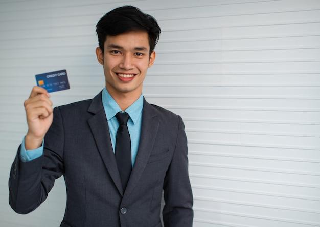 灰色の壁に対してクレジットカードを示すカメラに微笑んで幸せな若いアジア人男性起業家