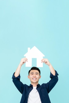 Happy young asian man holding house sign with copy space  overhead isolated on light blue wall for real estate concepts