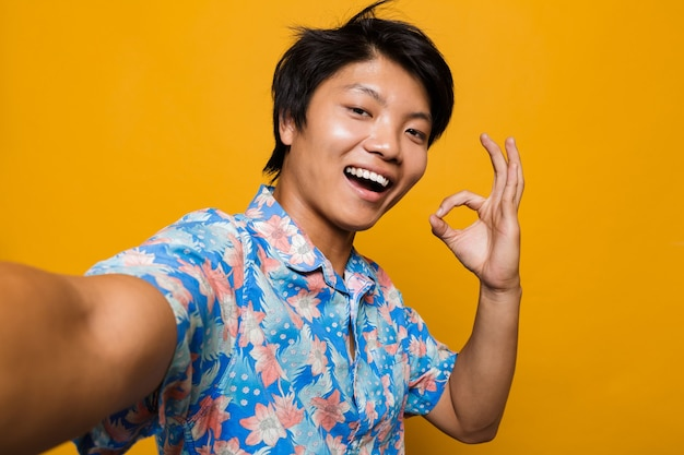 Happy young asian man posing isolated over yellow space take a selfie with okay gesture.