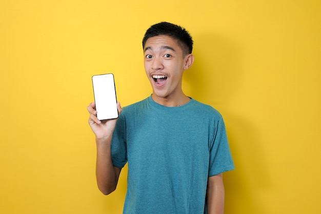 Happy young asian man showing white phone screen at camera, isolated on yellow background