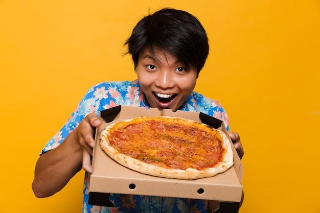 ピザを保持している黄色のスペースに孤立して立っている幸せな若いアジア人男性。