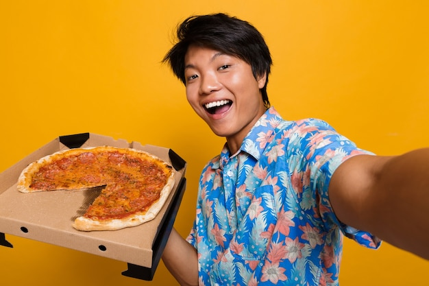 Happy young asian man standing isolated over yellow space eat pizza take a selfie by camera.