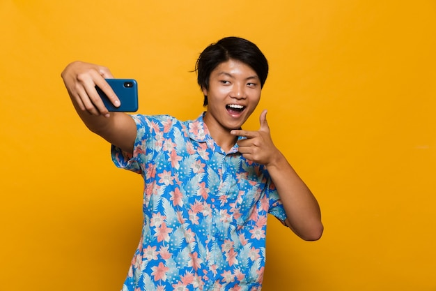 Happy young asian man standing isolated over yellow space take a selfie by mobile phone pointing.