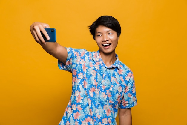 Happy young asian man standing isolated over yellow space take a selfie by mobile phone.