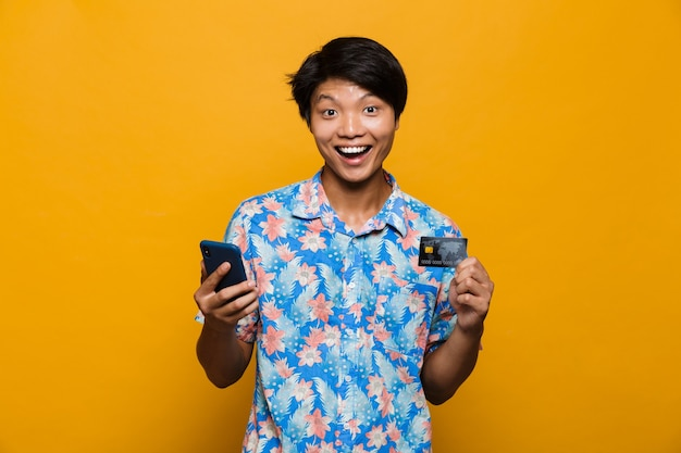 Happy young asian man standing isolated over yellow space using mobile phone holding credit card.