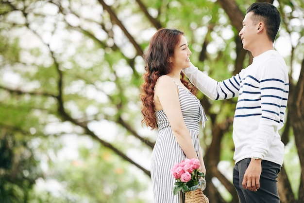 Happy young asian man touching face of his pretty smiling girlfriend when they are standing in park