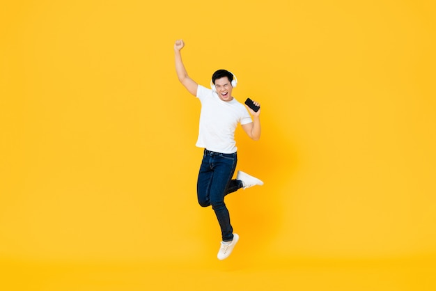 Happy young asian man wearing headphone listening to music from mobile phone and jumping with fist raising isolated on yellow wall