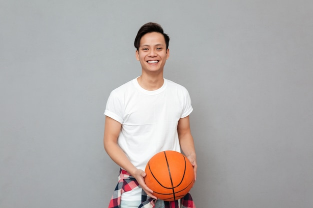 Happy young asian man with basket ball