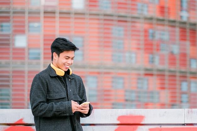 도시 거리에서 스마트폰을 사용하여 헤드폰을 끼고 행복한 젊은 아시아 남자