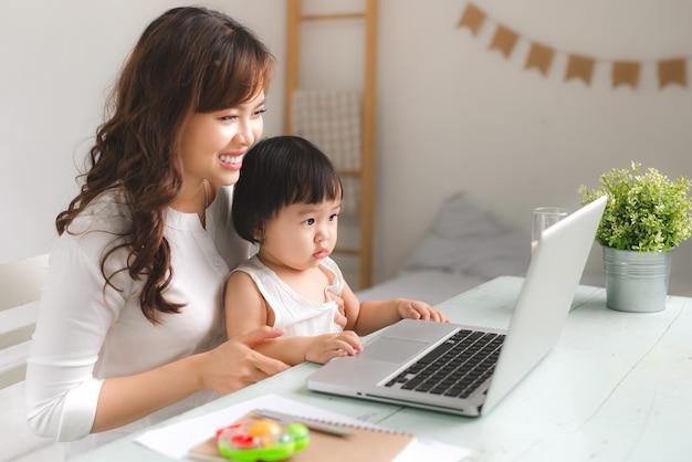 행복한 젊은 아시아 어머니와 그녀의 아기가 인터넷에서 게임을 하고 있습니다.