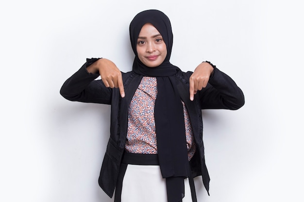 Happy young asian muslim woman pointing with fingers to different directions isolated on white