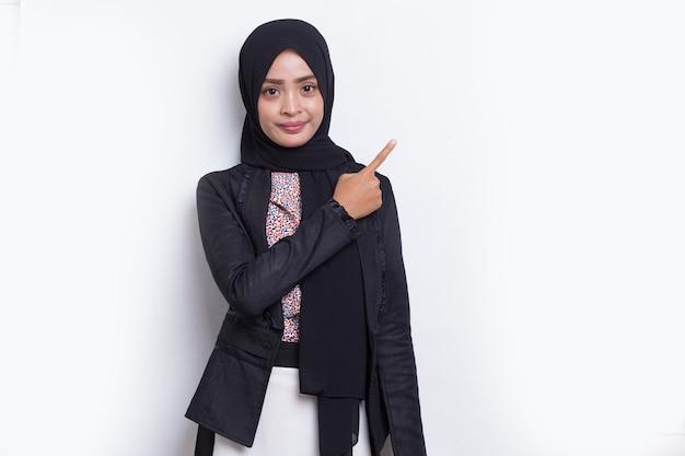 흰색으로 격리된 다른 방향을 손가락으로 가리키는 행복한 젊은 아시아 이슬람 여성