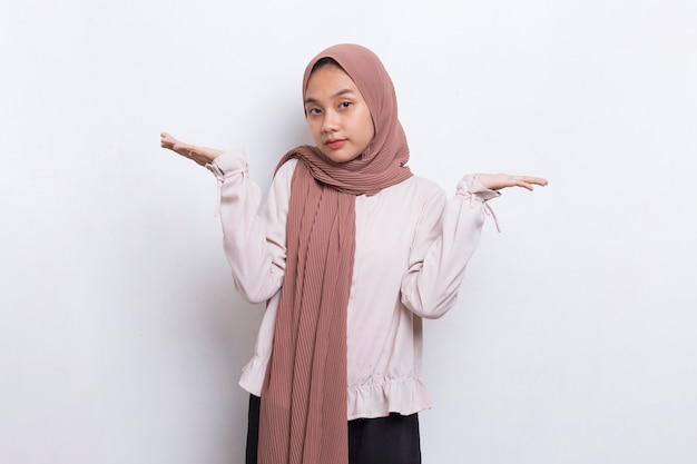 幸せな若いアジアのイスラム教徒の女性が白い背景の上のさまざまな方向に指で指しています