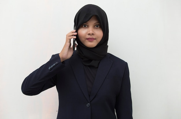 Happy young asian muslim woman using mobile phone