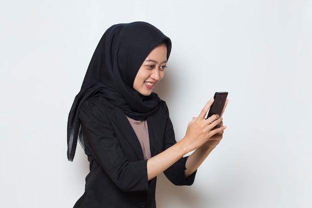 携帯電話を使用して幸せな若いアジアのイスラム教徒の女性