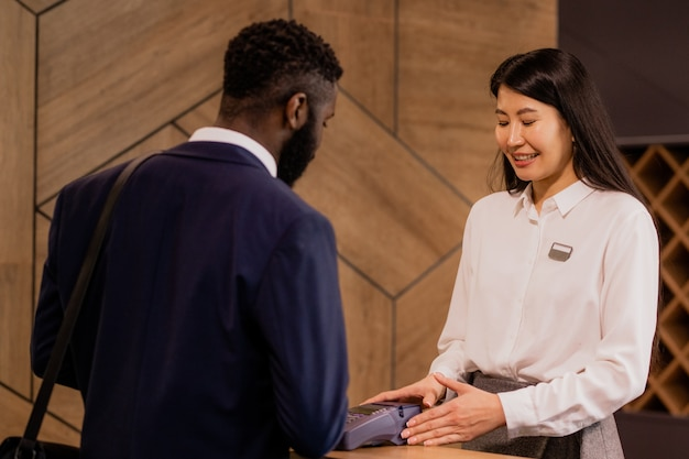 Happy young asian receptionist of hotel holding payment machine while serving one of guests by counter