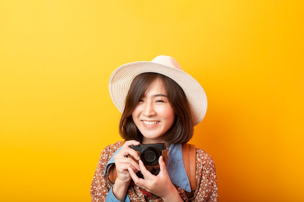 Happy young asian tourist woman on yellow wall