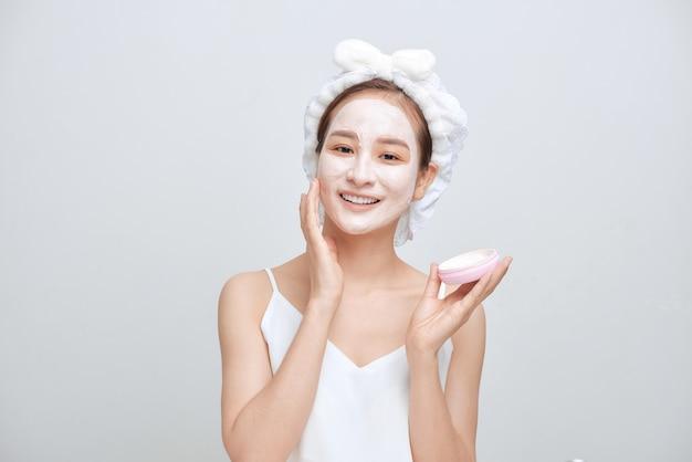 顔の粘土マスクを適用し、タオルを身に着けている幸せな若いアジアの女性。