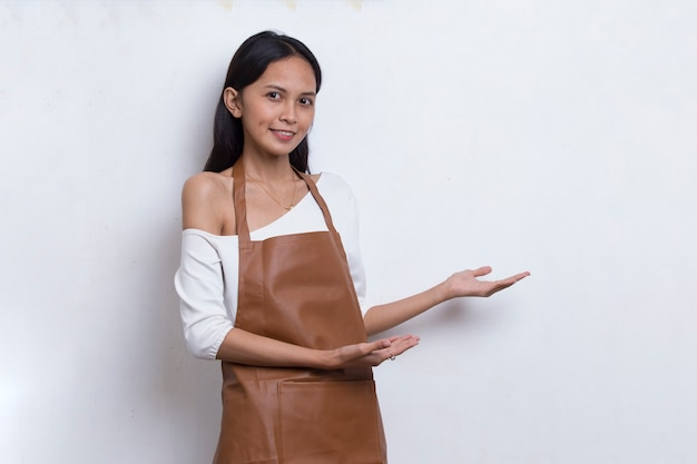 Счастливая молодая азиатская официантка бариста женщины указывая пальцами в разные стороны