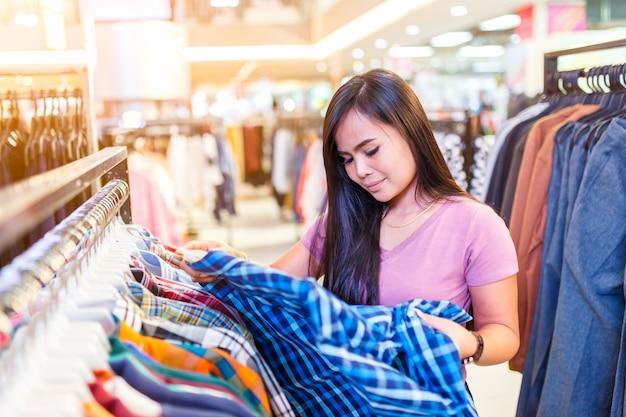 쇼핑몰이나 옷가게에서 셔츠에 가격표를 확인하는 행복 한 젊은 아시아 여자.