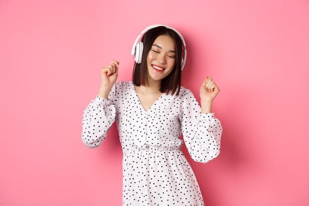 Felice giovane donna asiatica che balla e si diverte, ascoltando musica in cuffia, in piedi su sfondo rosa. copia spazio