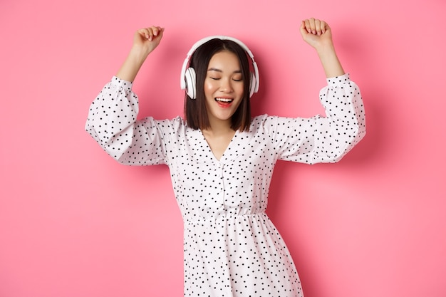 Happy young asian woman dancing and having fun, listening music in headphones, standing over pink.