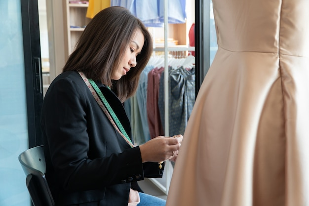 Happy young asian woman dressmaker fashion designer is checking for completion for a dress