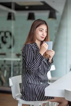 Кофе счастливой молодой азиатской женщины выпивая за столом с компьтер-книжкой в кафе.