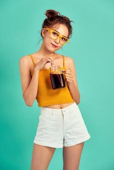 青で隔離のソーダを飲む幸せな若いアジアの女性。