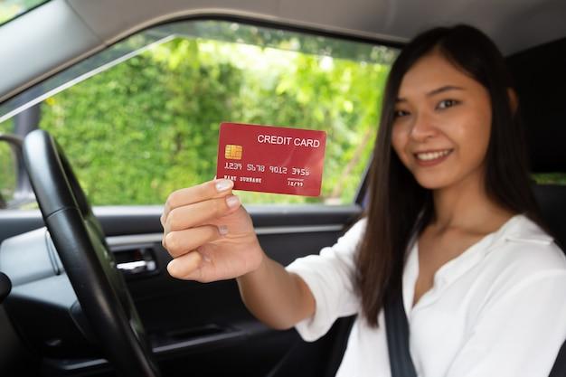 차를 운전하고 신용 카드를 손에 들고 있는 행복한 젊은 아시아 여성