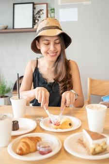 カフェの木製テーブルでクロワッサン、ケーキ、アイスコーヒーとデザートを食べる幸せな若いアジアの女性