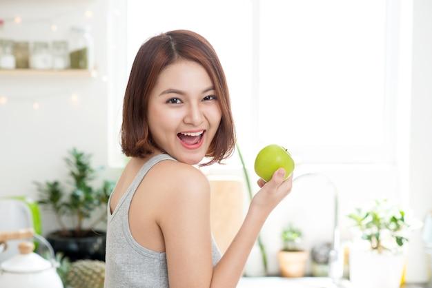 キッチンで青リンゴを食べる幸せな若いアジアの女性。ダイエット。ダイエットの概念。健康食品