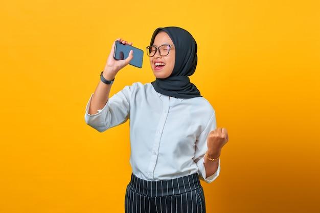 黄色の背景でスマートフォンを使用して歌を楽しんで幸せな若いアジアの女性