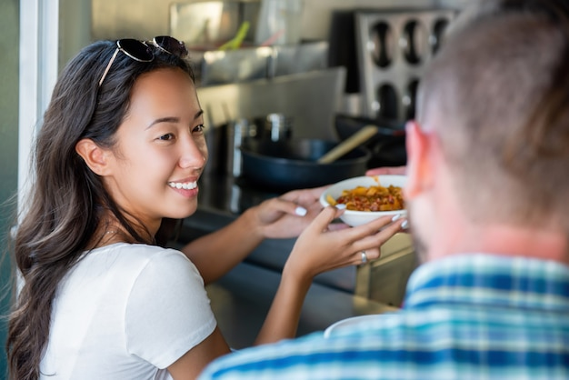 Happy young asian woman getting pasta from food truck