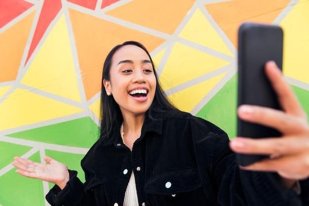 화려한 벽 옆에서 휴대폰으로 화상 통화를 하며 즐거운 시간을 보내는 행복한 젊은 아시아 여성