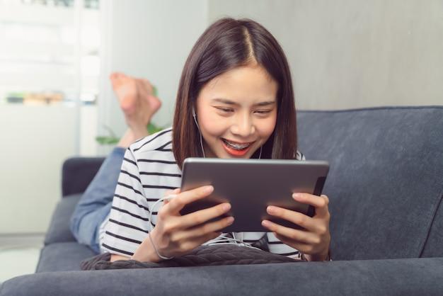 Счастливая молодая азиатская женщина держа цифровую таблетку и используя онлайн социальный образ жизни на софе в доме. технология для концепции коммуникации.