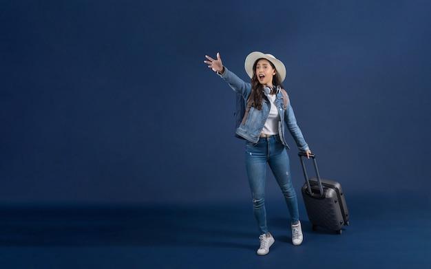 荷物を持って、青い色で空港に急いで幸せな若いアジアの女性