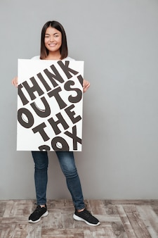 Happy young asian woman holding copyspace blank.