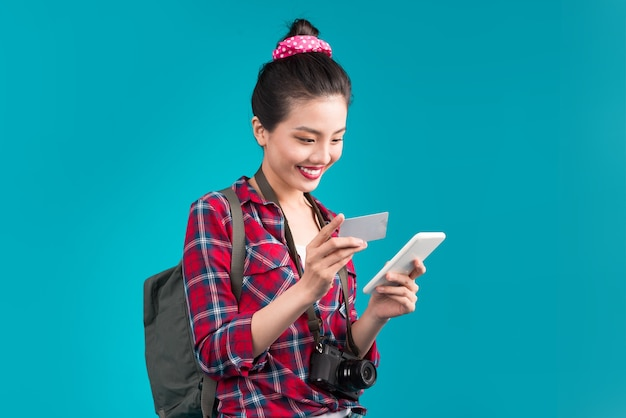 Happy young asian woman holding credit card and smartphone standing over blue.