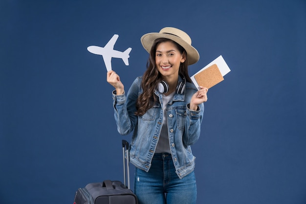 Happy young asian woman holding passport with boarding pass and airplane mockkup