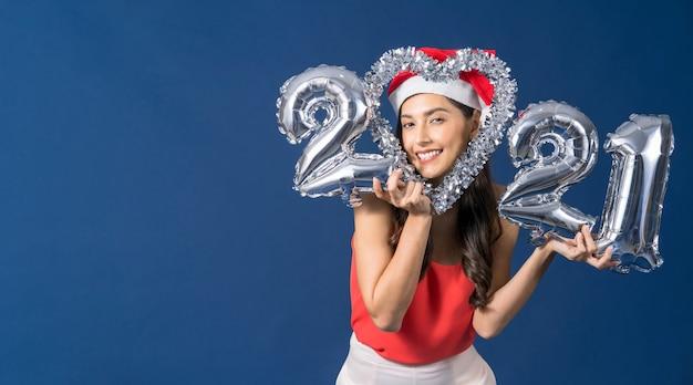 실버 컬러 풍선을 들고 행복 한 젊은 아시아 여자 파란색 배경에 메리 크리스마스와 새 해 복 많이 받으세요