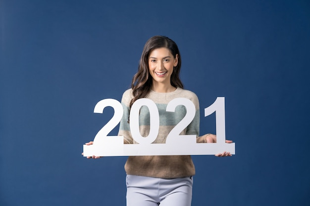 Happy young asian woman holding  white paper banner for celebrate merry christmas and happy new year on blue color background