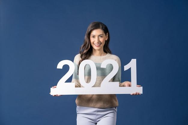 Счастливая молодая азиатская женщина, держащая белую бумагу для празднования рождества и счастливого нового года на синем фоне