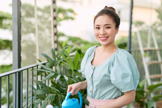 幸せな若いアジアの女性主婦バルコニーで花に水をまく