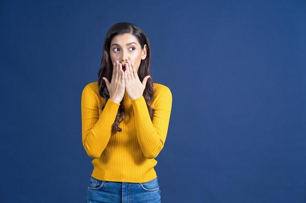 화려한 노란색 캐주얼 옷을 입은 행복한 젊은 아시아 여성이 파란색 콜로에서 소리를 지르며 험담을 합니다.